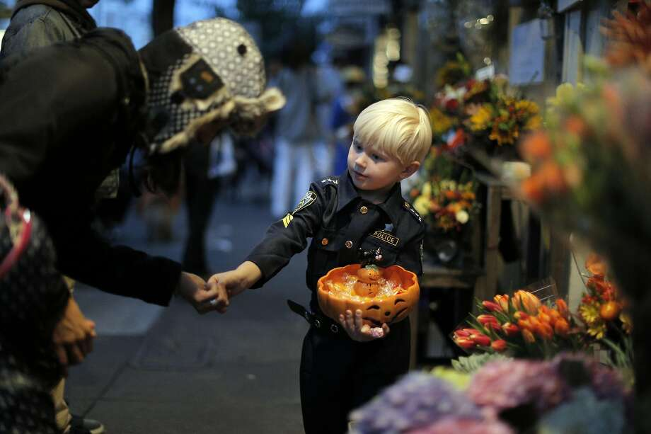 Vitaly Van De Sande, 4, hands out candy to passersby at his mom and grandmother's flower shop on 24th Street as the city celebrated Halloween.