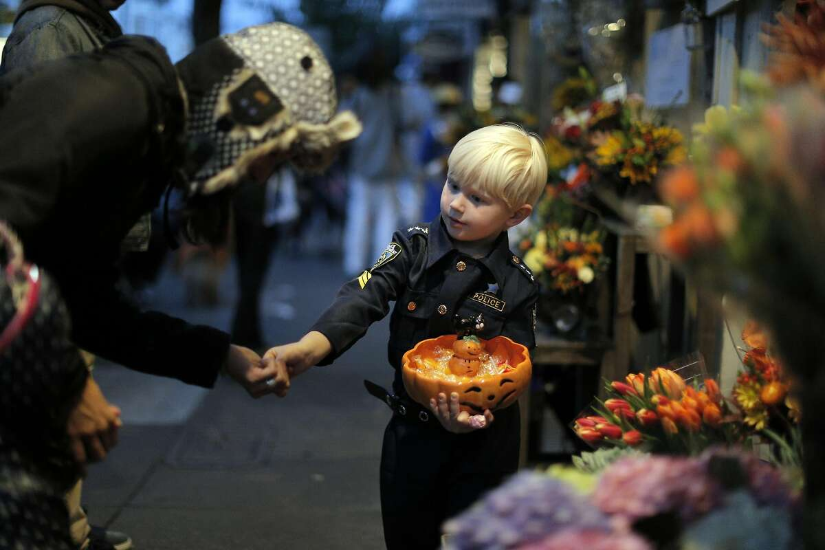Vitaly Van De Sande, 4, hands out candy to passersby at his mom and grandmother's flower shop on 24th Street as the city celebrated Halloween in San Francisco, Calif., on Monday, October 31, 2016.