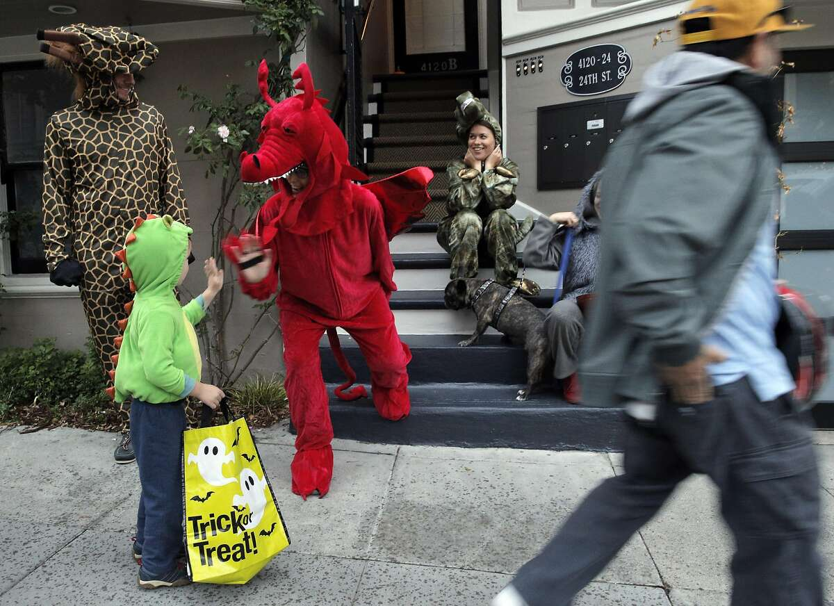 James McAnaney, 3, gets a high five from Laura Nikolic, dressed as a red dragon as he Trick-or-Treats on 24th Street in Noe Valley as the city celebrated Halloween in San Francisco, Calif., on Monday, October 31, 2016.