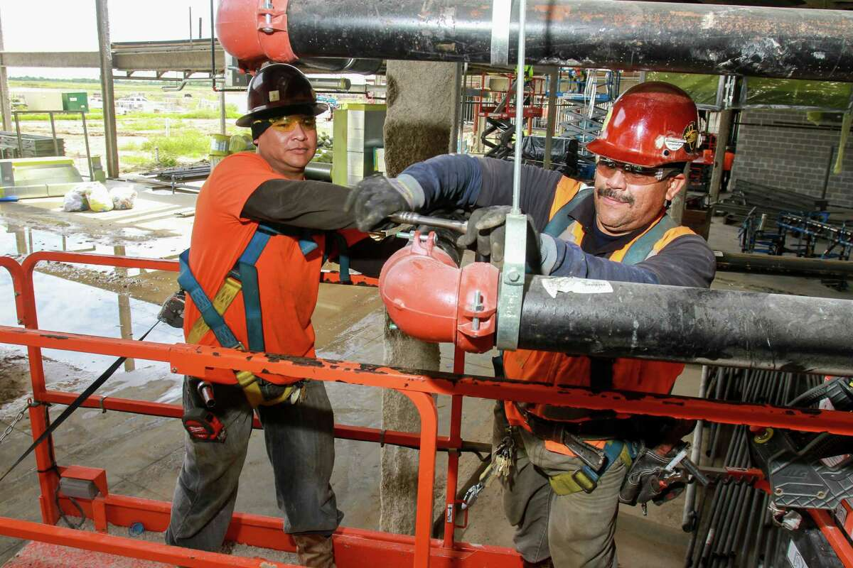 Neftali Mejia, left, and Alejandro Alvarado of Texas Saffire, installing a pipe coupling on a fire sprinkler system. This is part of the construction of the new Cypress-Fairbanks High School #12. (For the Chronicle/Gary Fountain, September 26, 2016)