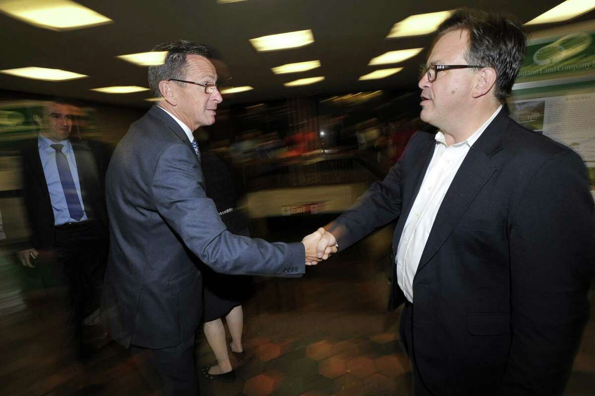 Gov. Dannel P. Malloy, left, shakes hands Frank Farricker during his unsuccessful campaign for Greenwich first selectman last year. Farrick is acting president of the Connecticut Lottery Corp.