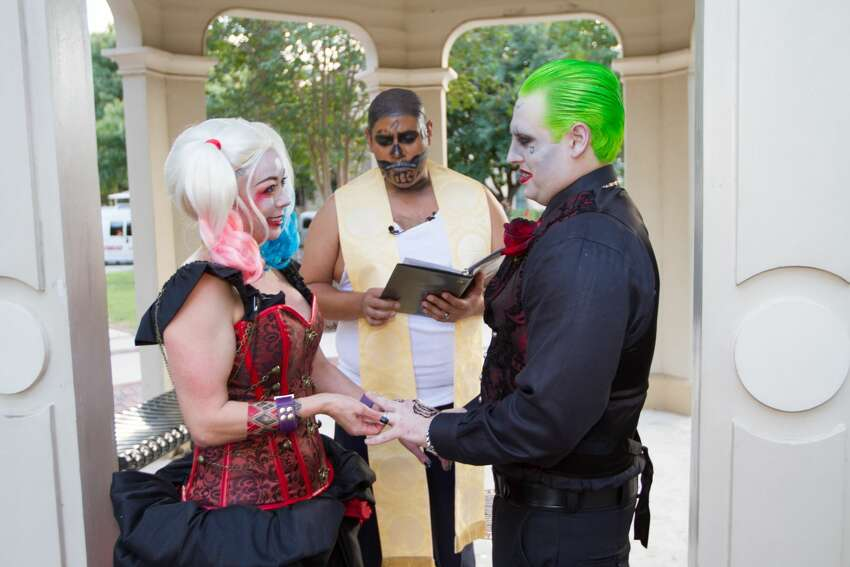 Nicole and John Fowler dressed as Harley Quinn and the Joker for their wedding at King William Park, surrounded by a their loved ones, also dressed as comic book characters.