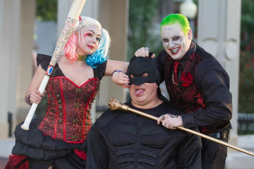Nicole and John Fowler dressed as the two villains for their wedding at King William Park, surrounded by a their loved ones, also dressed as comic book characters.