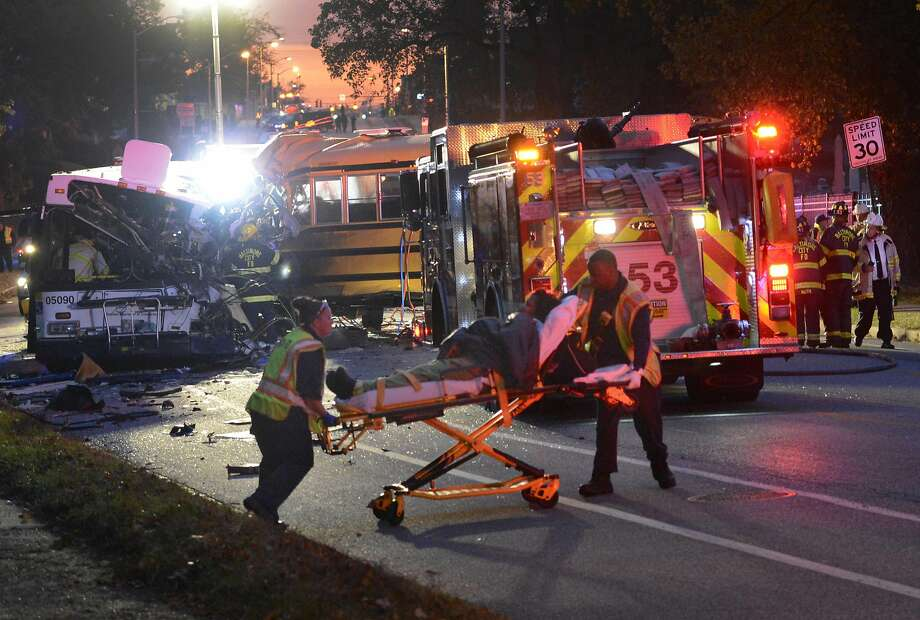 Fire and rescue officials are at the scene of a fatal collision involving a car, a school bus and a commuter bus in Baltimore. Photo: Jeffrey F. Bill, Associated Press
