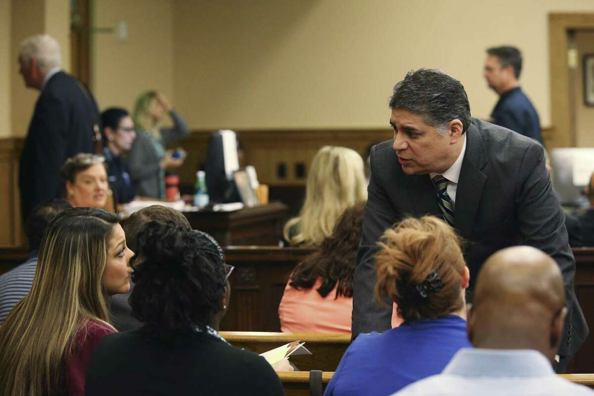 Lawyer Aric Garza talks with former Career Point College students before a hearing in their lawsuit against the college.