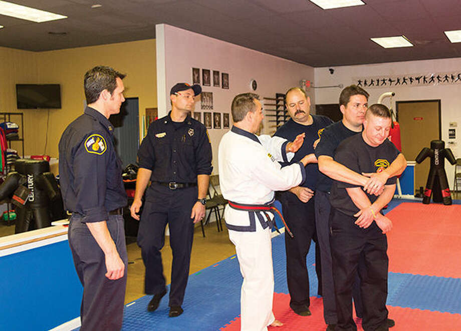 Edwardsville firefighters Captain Mark Mayfield, Tanner Sweetman and Captain James Whiteford, watch as Rick Grogan, owner of Grogan's Martial Arts Academy, uses firefighters Joey Cruz and Cory Heuchert to demonstrate a self-defense tactic.