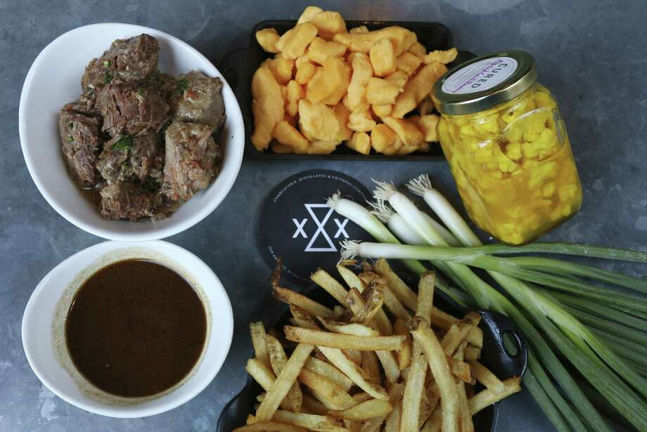 The elements of Cure's poutine: french fries, braised pig cheeks, gravy, cheese curds, pickled cauliflower and green onions. Photo: Jerry Lara /San Antonio Express-News / © 2016 San Antonio Express-News