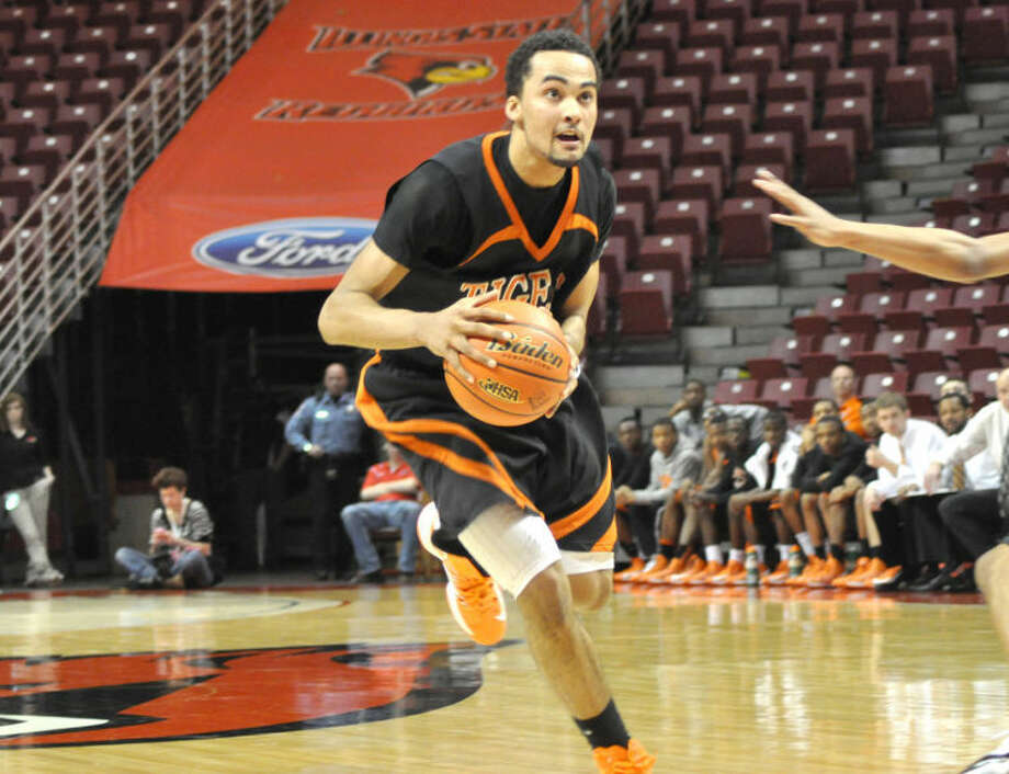 Tre Harris drives to the hoop on Tuesday as the Edwardsville Tigers defeated Chicago Heights Marian Catholic to advance to the Class 4A state tournament on Friday in Peoria.