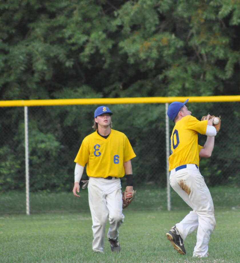 Edwardsville shortstop Chase McPeak, right, hangs on for a catch in short center field as teammate Jordan Heckler watches on in the second inning at Hoppe Park.