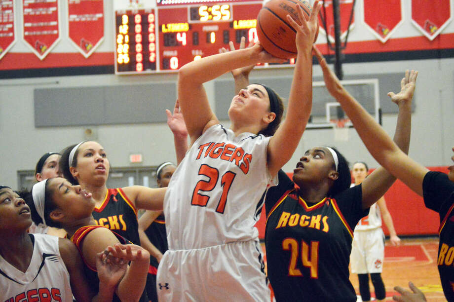 Edwardsville sophomore Rachel Pranger (No. 21) goes up for a shot in a crowd of players in the first quarter against Rock Island.