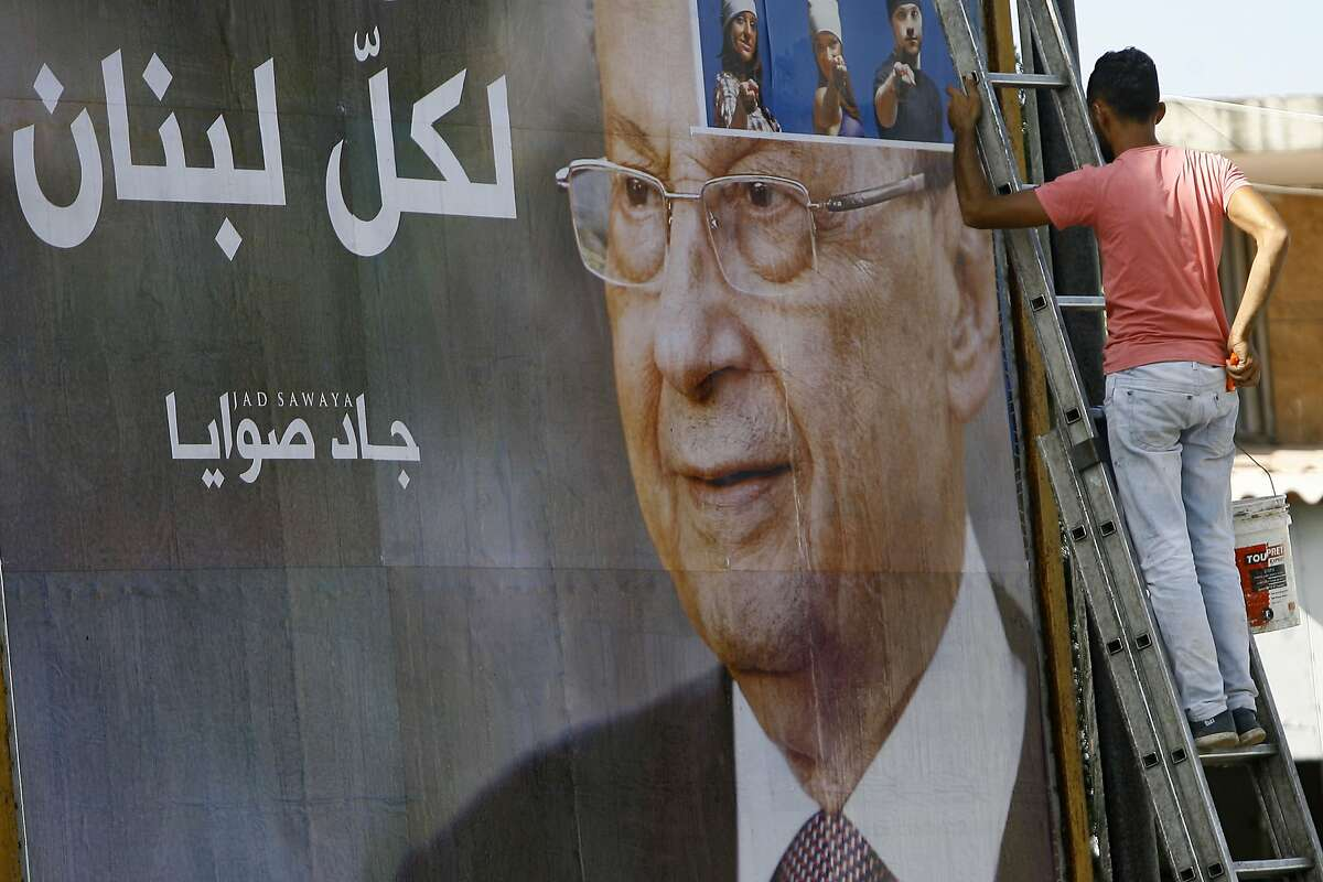 """A worker hangs a billboard showing Christian leader Michel Aoun with Arabic that reads """"For all Lebanon,"""" in the southern port city of Sidon, Lebanon, Sunday, Oct. 30, 2016. Aoun, an 81-year-old veteran Christian politician, is set to be elected by Parliament on Monday as part of a political deal that's expected to be another boost for President Bashar Assad in neighboring Syria. (AP Photo/Mohammed Zaatari)"""