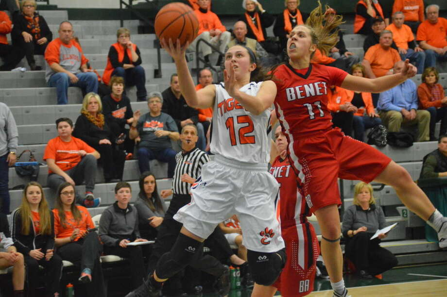Edwardsville guard Makenzie Silvey goes up for a layup with Benet Academy's Kathleen Doyle guarding her.