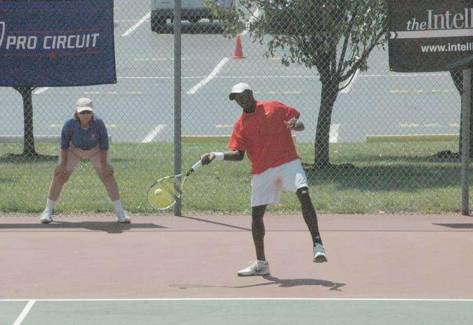 Blake Strode returns a shot against Evan King in the singles championship of the Edwardsville Futures on Sunday at the EHS Tennis Center.
