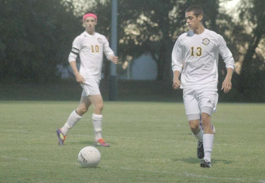 Knight Michael Babcock, right, prepares to pass the ball with teammate Matt Rankin, left, looking on. MELHS defeated Lebanon 2-0 on Thursday at home.