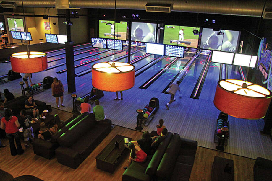 Friends and family experience the boutique bowling at Edison's Entertainment Complex's soft opening Wednesday night. Edison's features twelve lanes fused with black light effects, specialty lighting and a sound system with four projection screens spanning the lanes.