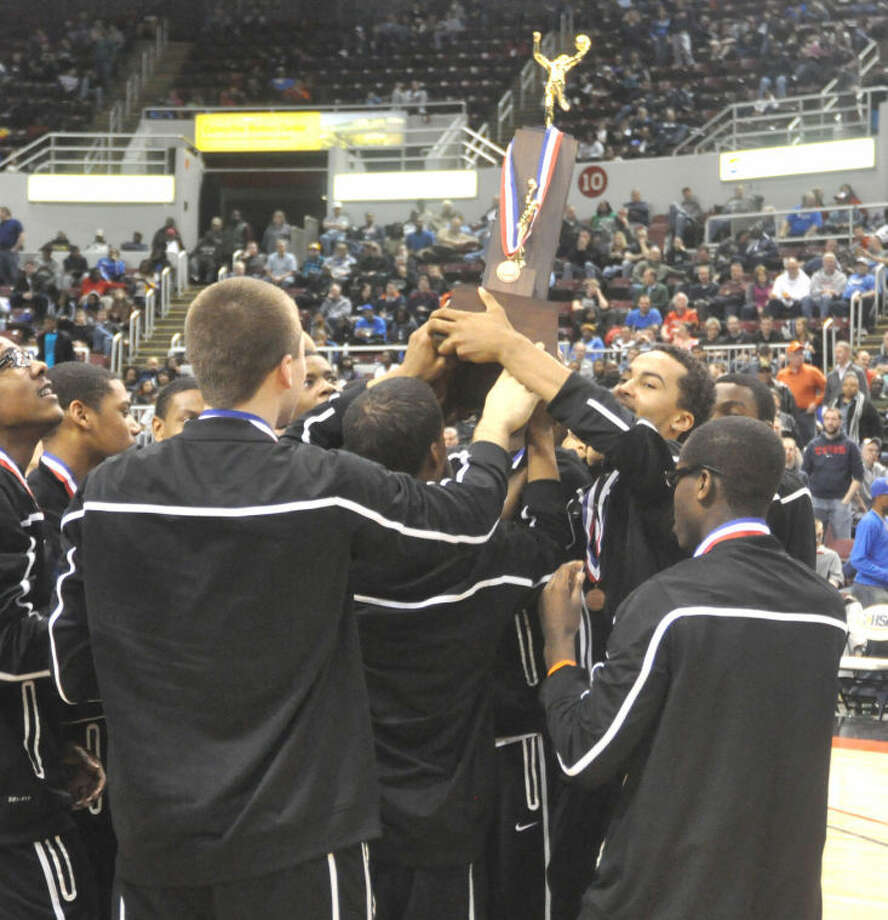 The Edwardsville Tiger boys' basketball team celebrates with their Class 4A third-place trophy from the state tournament on Saturday at the Peoria Civic Center.