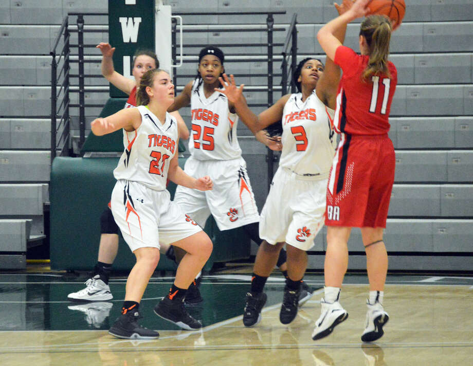Edwardsville's Rachel Pranger (No. 21), Criste'on Waters (No. 25) and Aaliyah Box (No. 3) try to defend Lisle Benet Academy's Kathleen Doyle during the Class 4A super-sectional game.