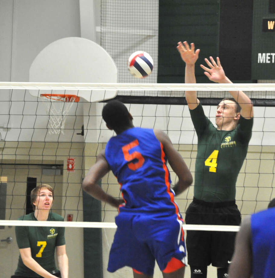Metro-East Lutheran's Thomas Schroader, right, goes up for a block on East St. Louis' Rashon Clark during Monday's match at MELHS.