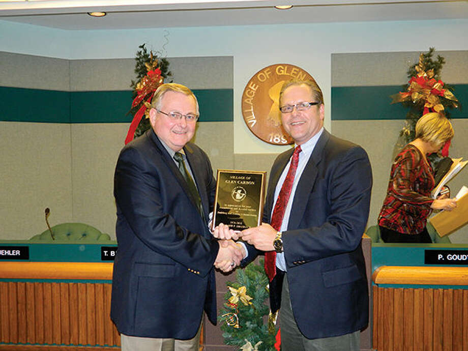 Glen Carbon Building and Zoning Administrator Will Shashack, left, receives a plaque recognizing his 35 years of service from Mayor Rob Jackstadt during a ceremony in December, 2011.