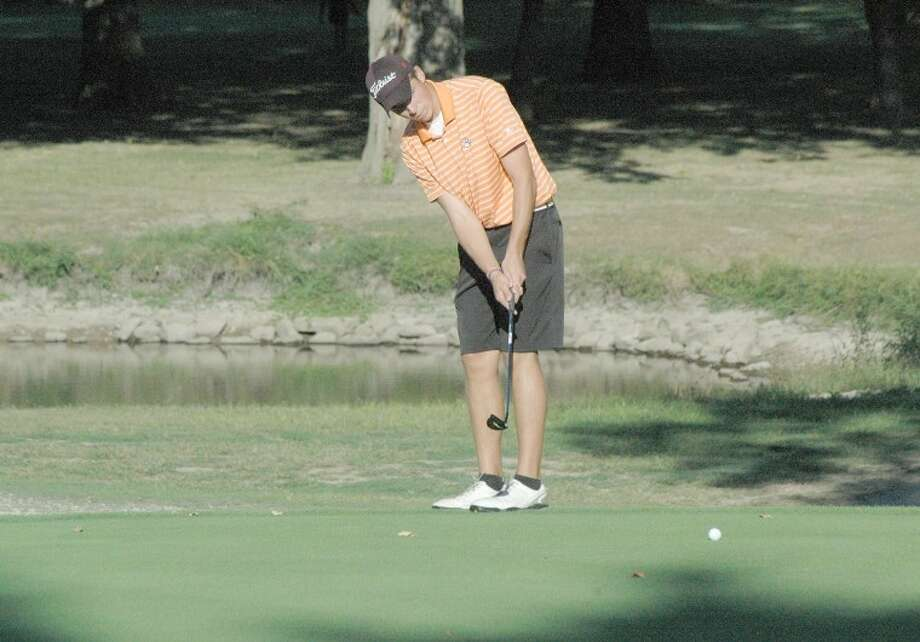 Edwardsville Tiger junior Drew Curtis watches his putt at Oak Brook Golf Club on Monday. The Tigers won a triangular event against the Alton Redbirds and the Triad Knights.