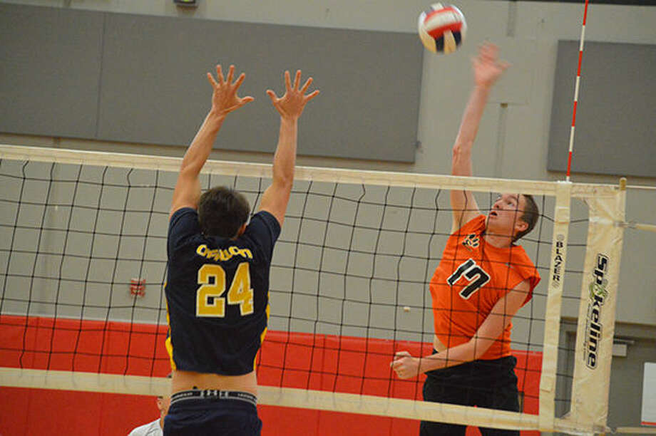Mike Horton goes for a spike, while O'Fallon's Parker Roustio goes for a block.