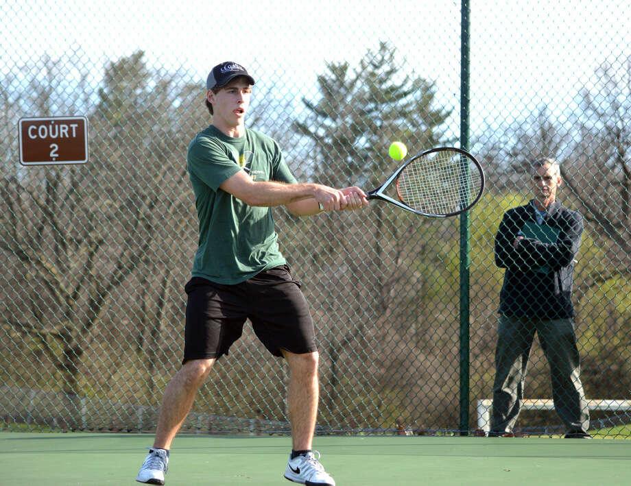 Metro-East Lutheran senior Joel Eberhart hits a backhand during Thursday's match against Hillsboro's Seth Watson at No. 2 singles.
