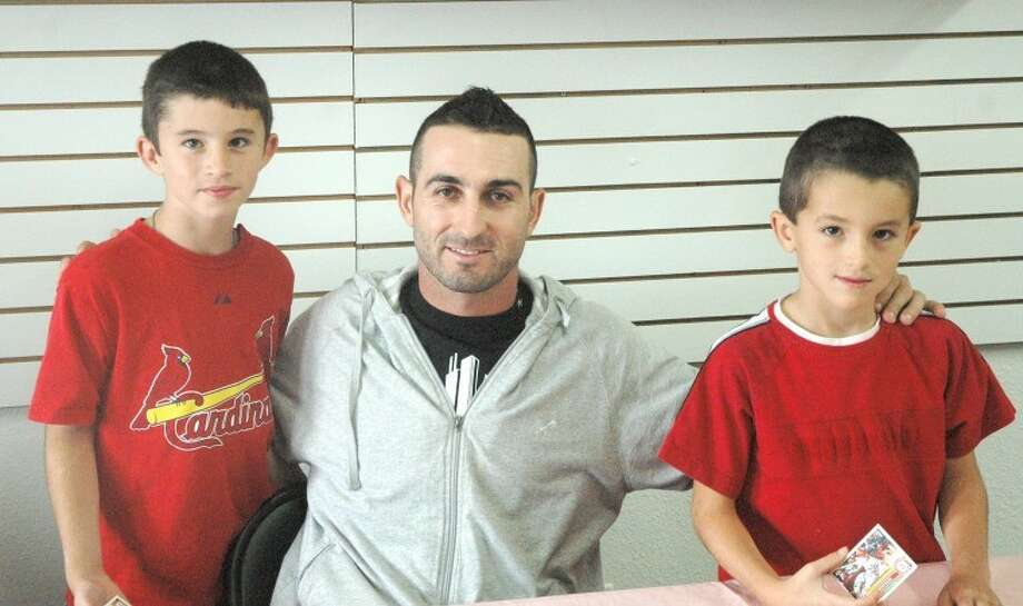 Daniel Descalso of the St. Louis Cardinals takes time out of the current Cardinal pennant race to pose with a pair of young Redbird fans. Descalso visited Good Sports Sports Cards and Memorabilia early Saturday afternoon for an autograph signing session. Photo: Erik Hand