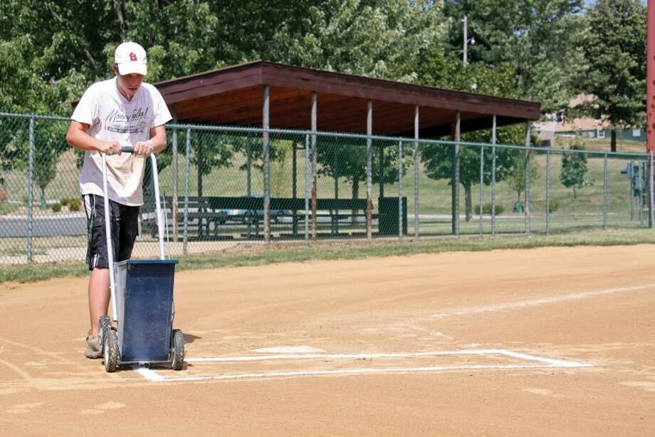 Nick Santoro sweats it out as he focuses on chalking the field at one of Hoppe Park's baseball diamonds Thursday afternoon. Thursday's temperatures climbed above 100 again making any outdoor job in the blazing sun a chore