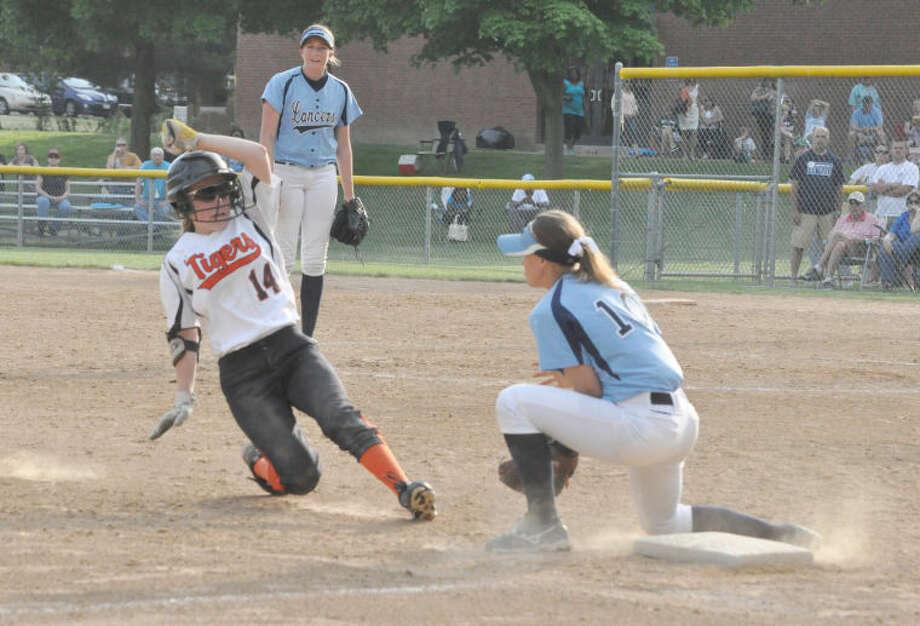 Edwardsville freshman Rachel Anderson slides safely into third base during the seventh inning against the Belleville East Lancers in Belleville.