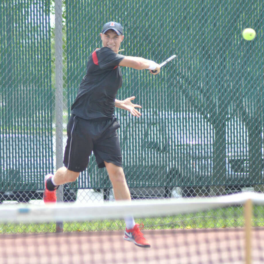 The University of Illinois' Tim Kopinski smashes a return in the men's open singles finals Sunday at the EHS Tennis Center.