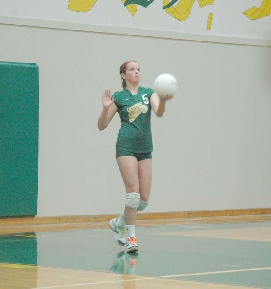 Knight sophomore Anna Kellar prepares to serve against Marquette on Monday at Hooks Gym. MELHS won 2-0.