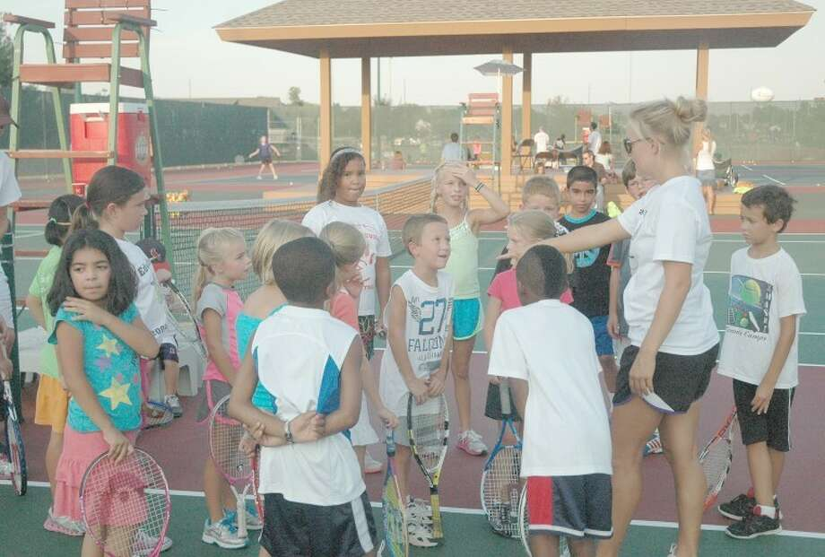 Edwardsville girls' tennis assistant coach Stephanie Clark instructs a group of second, third and fourth graders how to play doubles at Kids' Night at the Futures on Tuesday at the EHS Tennis Center.