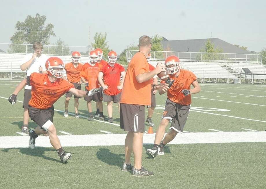 Edwardsville football coach Matt Martin, center, acts as the quarterback during defensive drills at the District 7 Sports Complex on Wednesday.