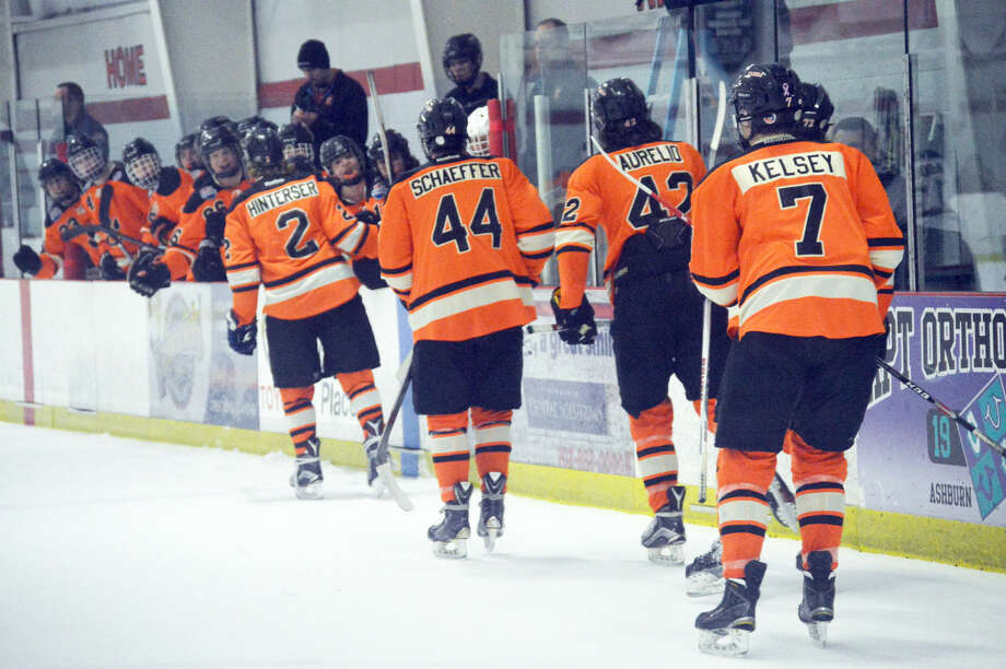 The Edwardsville hockey team celebrates after a goal by Tyler Hinterser (No. 2) during the opening game against Stoneman Douglas, Fla., in Reston, Va.