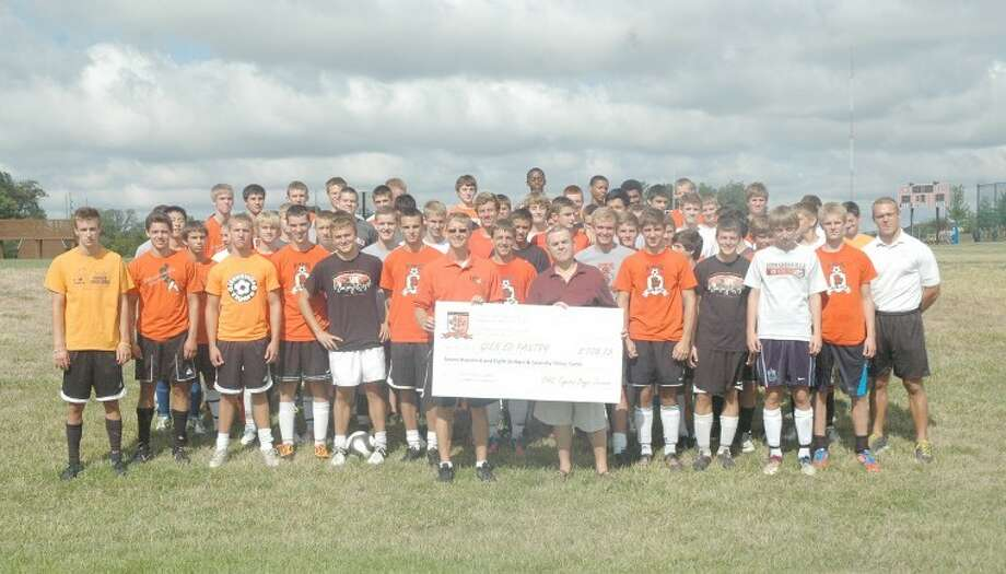 The Edwardsville boys' soccer team presented a check for $708.73 to the Glen Ed Pantry on Friday. EHS head coach Mark Heiderscheid, front, is pictured with Bob Vollmar of the Glen Ed Pantry. The Tigers raised the money during an annual community service car wash and they donated the proceeds from the event for school supplies.
