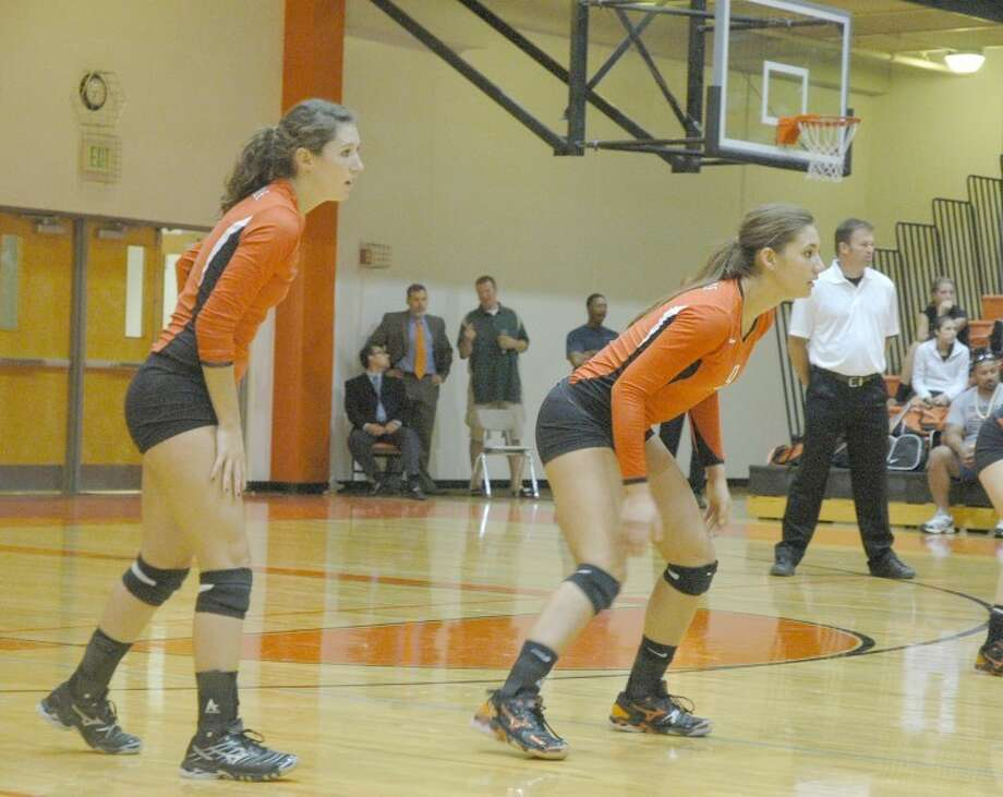 Edwardsville's Lexi Gober, left, and Sam Epenesa, right, prepare for Belleville East to serve during the first set on Thursday at Lucco-Jackson Gymnasium.