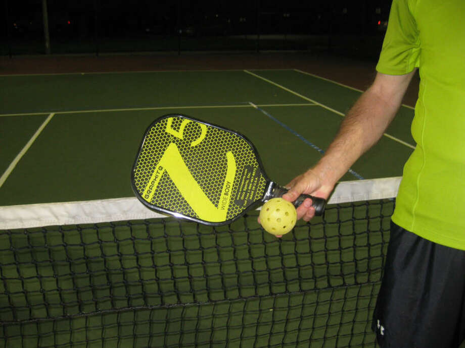 The paddle and pickleball are displayed recently with the court in the background set up for the game. The Village of Glen Carbon has applied for a grant to have a pickleball court installed for Phase II of Ray M. Schon Park.