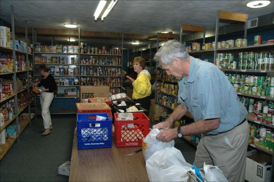 Volunteers Carol Vanderwaal, left, and Don McQueen prepare orders at the Glen Ed Pantry Monday. Evelyn Schaake, center, a board member, had stopped by with some donations. Photo: Oliver Wiest/Intelligencer