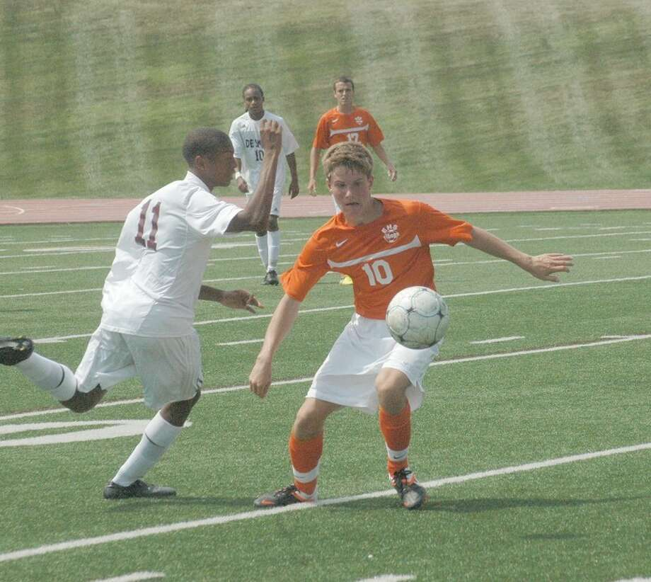 Edwardsville midfielder Landon Paul attempts to settle the ball while being defended by De Smet's Kaleb Jackson.