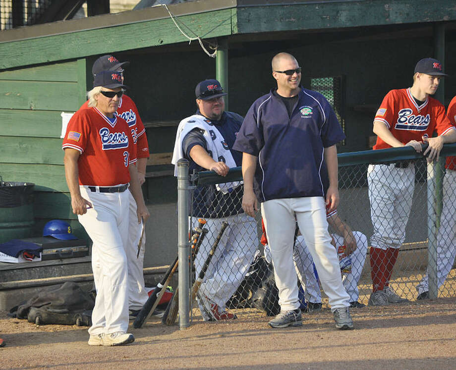 Metro East head coach Ken Schaake, left, assistant coach Nick Smith, center, and pitching coach Tim Stunkel look on from the dugout during Wednesday's game against Belleville in Alton.