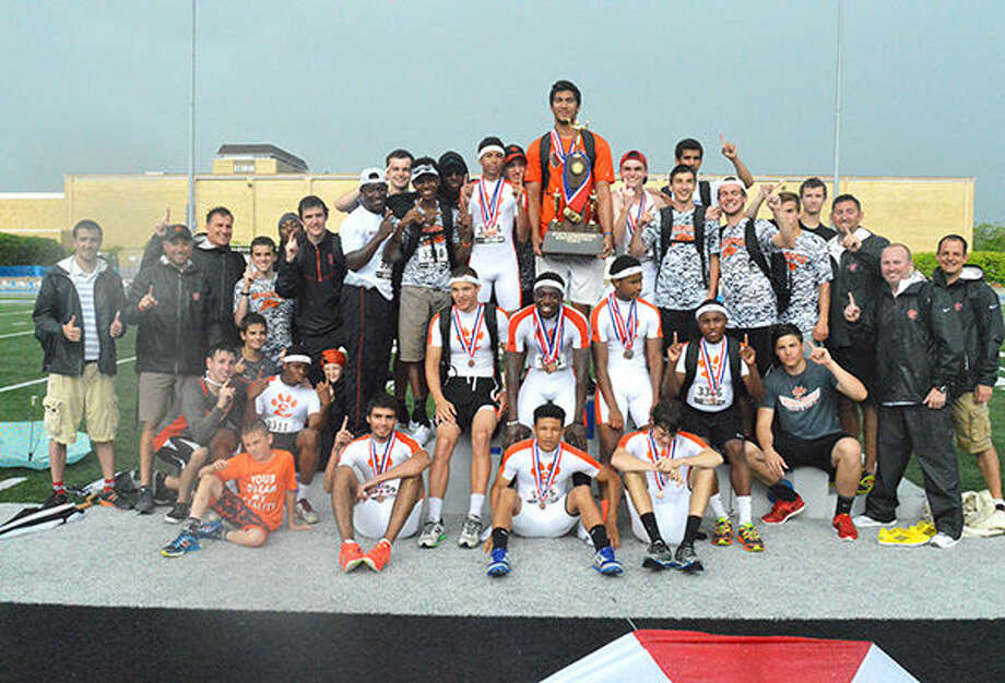 The Edwardsville boys' track team celebrates after winning the Class 3A state title.