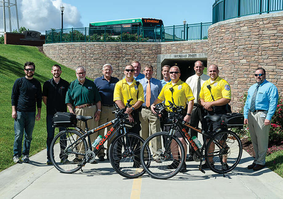 Employees from The Cyclery and Fitness Center, Chairman of the MCT Board of Trustees Dan Corbett, MCT Managing Director Jerry Kane, members of the Edwardsville Police Department, Edwardsville Mayor Hal Patton and City Administrator Tim Harr pose for a picture with the two donated bikes on the Nickel Plate Trail. Photo: Matt Winte/Intelligencer