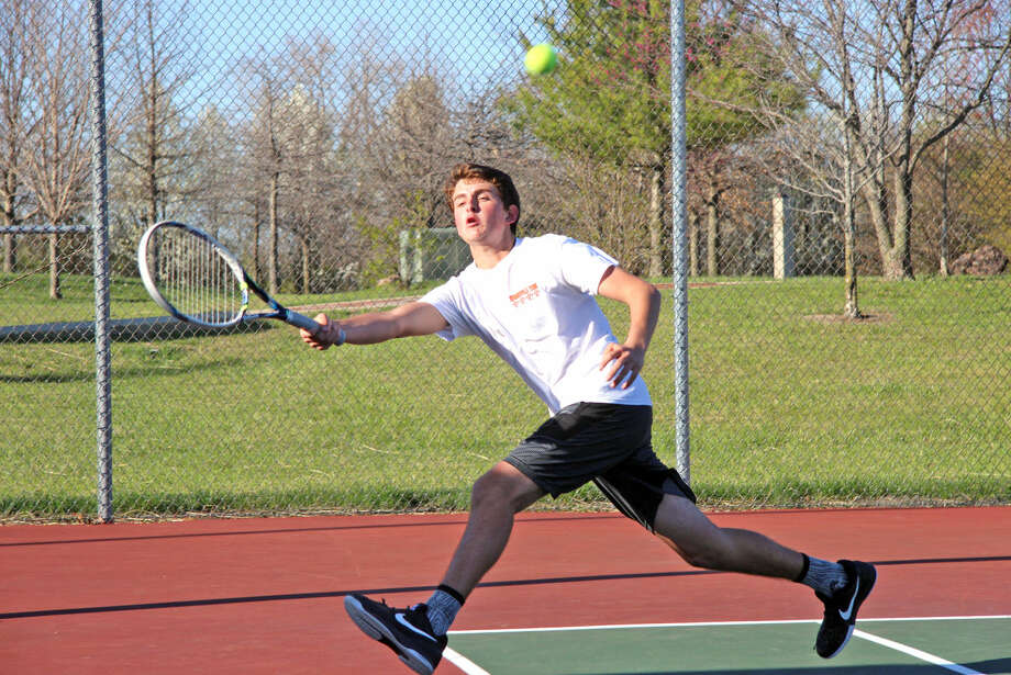Edwardsville junior varsity player Logan Kuhns chases down the ball during his No. 2 doubles match against Metro-East Lutheran on Monday.