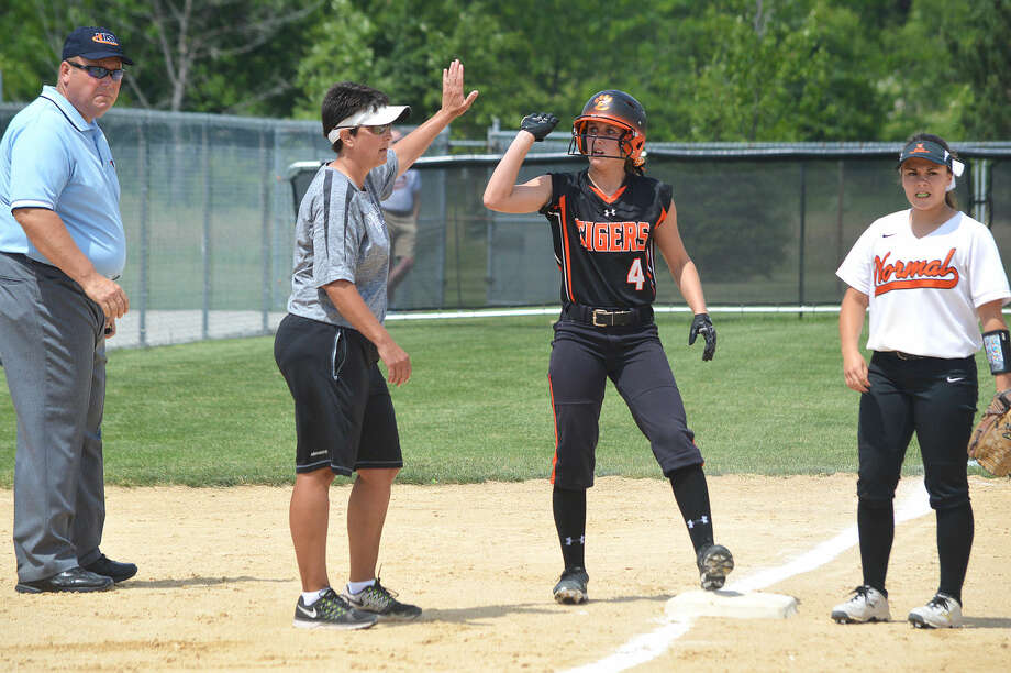 Edwardsville senior Ari Arnold (4) gets a high-five from coach Lori Blade after Arnold reached third base in the 12th inning of Saturday's sectional final at Normal. The Tigers scored two runs in the inning to beat Normal Community.