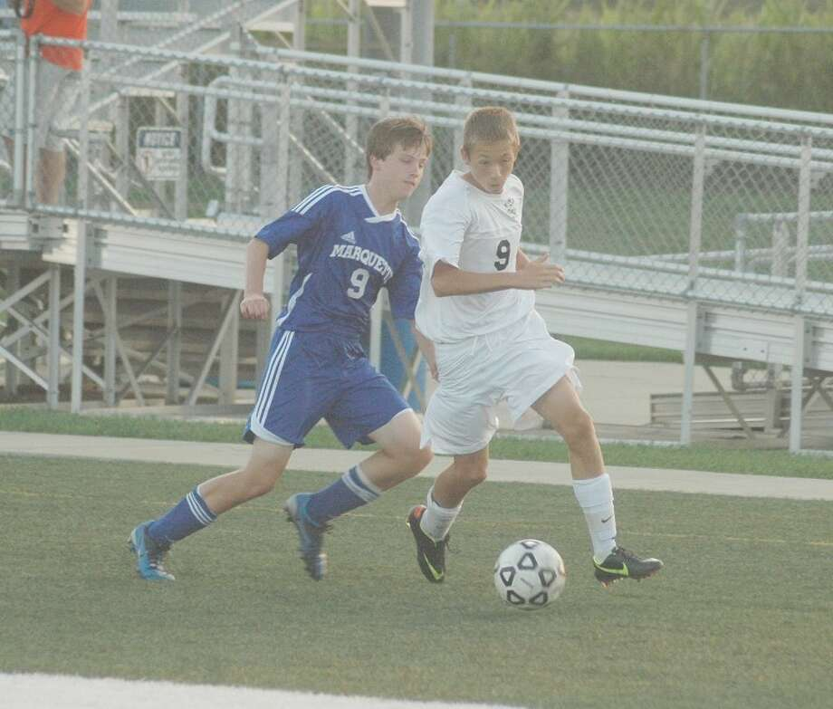 Edwardsville freshman Tom Giacobbe, right, works past a Marquette defender during first-half action on Monday. EHS won 7-1.