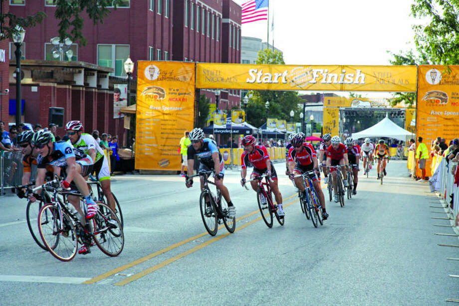 Cyclists prepare to make the turn from Main Street on to Vandalia Street during the Men's Category 4 race at the Fourth Annual Stifel Nicolaus Rotary Criterium on Saturday.