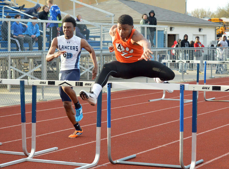 Edwardsville junior Daval Torres competes in the second leg of the 440-meter shuttle hurdle relay Friday at the 50th annual O'Fallon Relays.