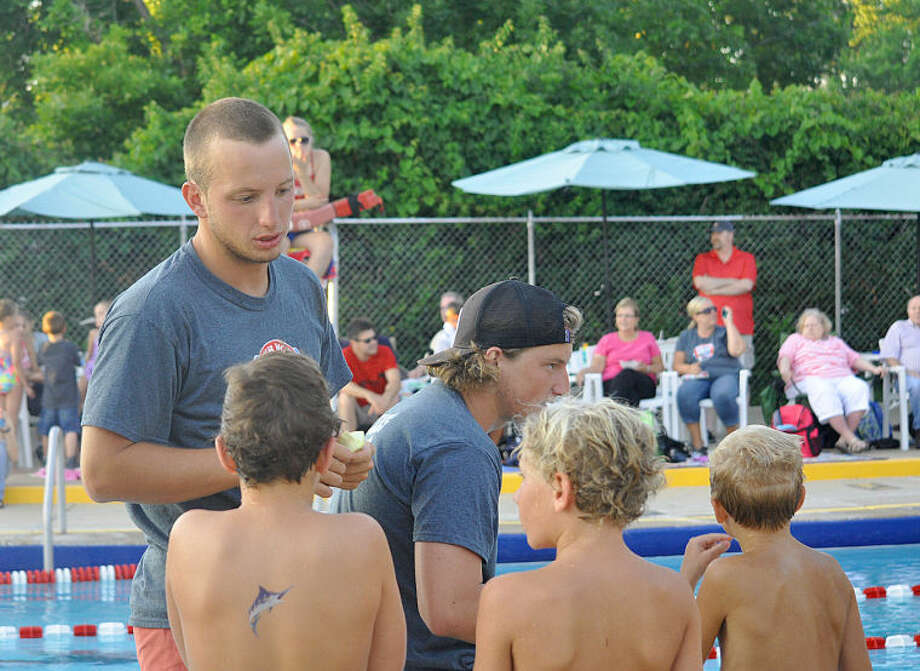 Former Edwardsville standout swimmer Max Byers talks with some of his Marlin swimmers during a meet this season. Byers returns to Edwardsville to coach at Water Works during the summer after swimming for Penn State during the school year.