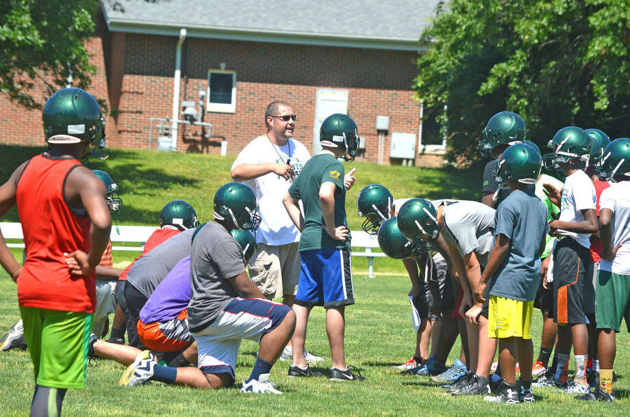 Metro-East Lutheran football coach Matt Tschudy talks to his players Wednesday during practice. This is the first season that MELHS and Madison are playing together as a co-op program.