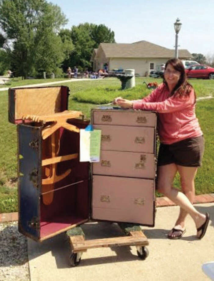 Rebecca Harper stands next to her 1900s antique wardrobe steamer trunk for sale at this year's community yard sale held on Saturday in Holiday Shores. This year many items were listed on Facebook for pre-sales. Photo: Laura Scaturro/Intelligencer